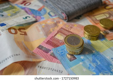 Wallet left on top of various euro bills and coins