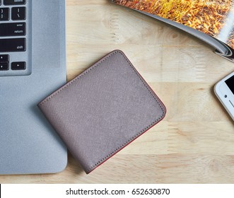 Wallet, mobile phone and laptop on wooden table.