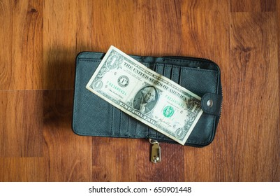 Wallet and money con wooden wall,selective focus.
