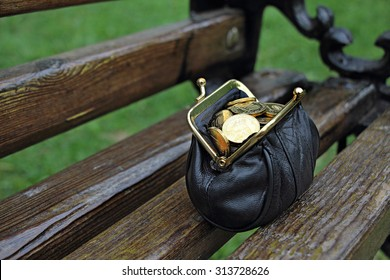 Wallet with money found on a park bench. A purse full of coins.