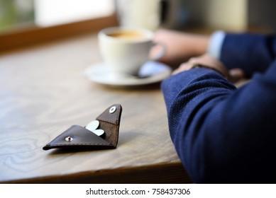 wallet near man drinking coffe