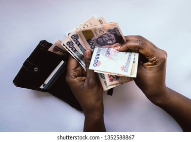 Wallet with Nigerian naira notes and African woman's hand holding naira notes. Wallet with cards and money for personal finance concept