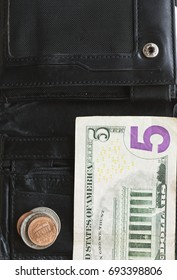 Wallet with small change cash. American dollars on black, plain wallet.