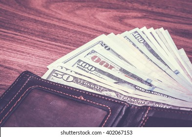 Wallet with us dollar bills on wooden table. toned image
