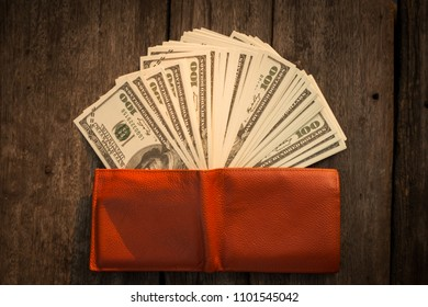 Wallet with US dollars on wood table , Money with leather orange wallet
