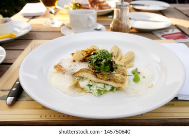 Walleye fillet with artichokes and molecular broth on restaurant table
