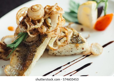 Walleye on the grill with onions on a white plate on a wooden table
