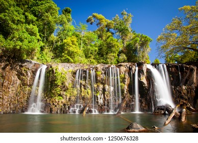 Wallicher Falls, Wide tropical waterfall with multiple streams of water falling over cliff in lush green rainforest, Queensland Australia.