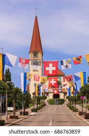 Wallisellen, Switzerland - 30 July, 2017: street decorated with flags for the upcoming Swiss National Day, the protestant church in the background. Wallisellen is a town in the Swiss canton of Zurich.