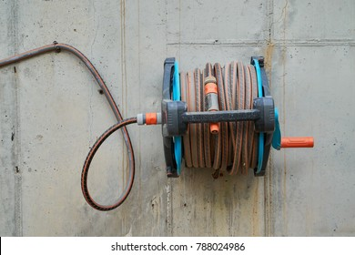 Wall-mounted hose roll for gardening on a exposed concrete finishing wall.