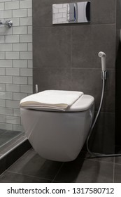 Wall-mounted toilet with shut-off set and a towel on a seat in a hotel bathroom
