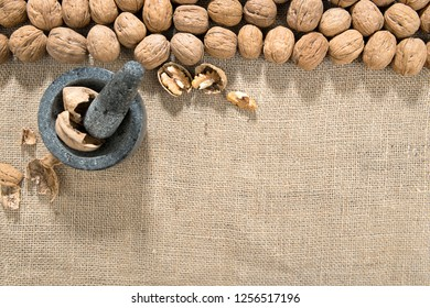 Wallnut, Mortar and Pestle over Jute Background