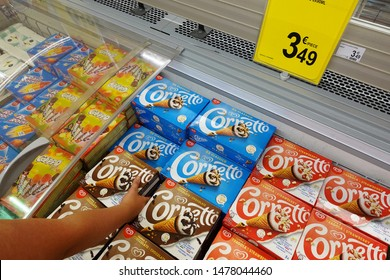 WALLONIA, BELGIUM - JULY 24, 2019: Shopper select a box Cornettos in a freezer with ice cream products in a Carrefour Hypermarket. Cornetto is a branded frozen dessert cone manufactured by Unilever.