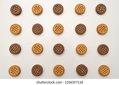 wallpaper. Chocolate and vanilla cookies with cream on a white background. View from above