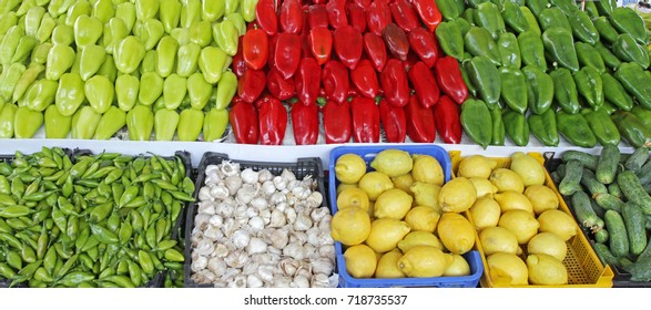 Wallpaper or cover photo of colorful organic vegetables and fruits on a market, green and red peppers, garlic, lemon, cucumbers, chilies. Fresh and organic healthy vitamin vegetables. Detox, antioxida