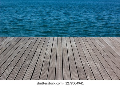 wallpaper pattern background surface texture of wooden deck floor perspective foreshortening  and vivid blue sea water, empty space for copy or text