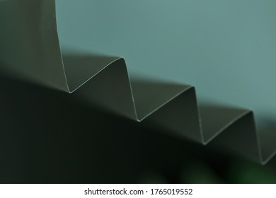 Wallpaper phone background. dark green zigzag abstract background.Sharp crankle surface.blurry scalloped texture.