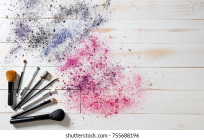 Wallpaper for professional makeup and fashion accessories with blush and eyeshadow brushes with smashed colorful pigments, white wooden background, copy space, above view