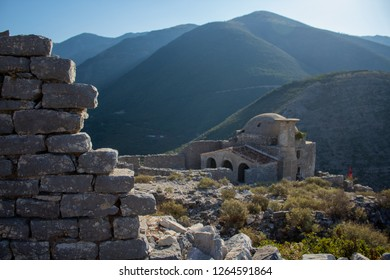 walls of a Albanian castle ruins and a very old Muslim original authentic ottoman mosque with the view of mountains in the background. located in south albanian riviera. borsh vlore albania vlora