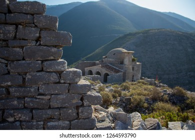 walls of a Albanian castle ruins and a very old Muslim original authentic ottoman mosque with the view of mountains in the background. located in south albanian riviera. road to saranda