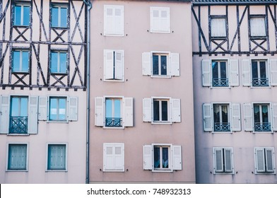 The walls of the french tenement house separated in three sections, decorated with the shutters