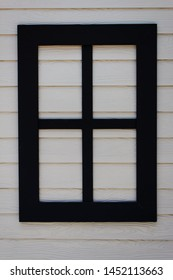 The walls are made from fiber cement, stacked together and decorated with black window frames.