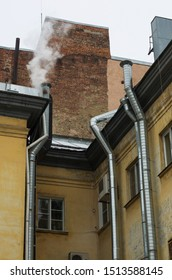 Walls of old houses with silvery pipes ventilation system with smoke over one of the pipes vertical orientation
