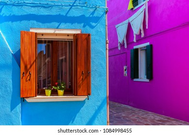 Walls painted in vivid colors with windows and wooden shutters in Burano, Italy.