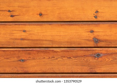 Walls of planks are arranged in color paint orange. Wooden texture closeup as a background