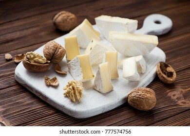 walnut with brie cheese on wooden table. milk product background
