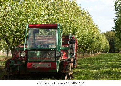 The walnut harvesting machine parked underneath the walnut trees on there grass, the machine is about to be used to harvest the crops in the walnut orchards of the Dordogne. (Point of focus machine).