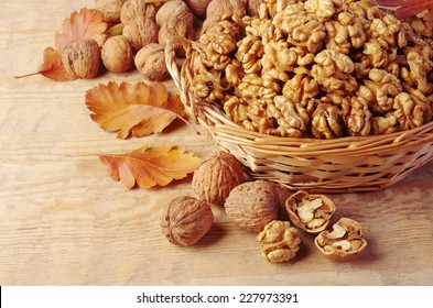 Walnut kernels in basket and whole walnuts on rustic old wood