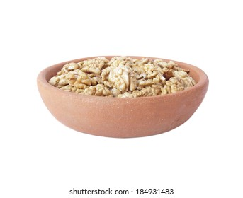 Walnut kernels in clay bowl isolated over white background