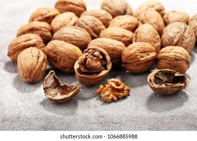 Walnut kernels and whole healthy walnuts on rustic old table - Shutterstock ID 1066885988