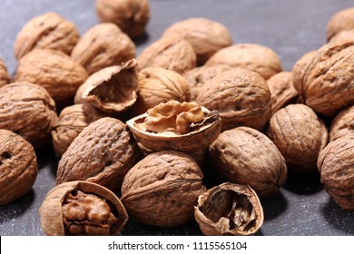 Walnut kernels and whole healthy walnuts on rustic old table - Shutterstock ID 1115565104
