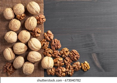 Walnut kernels and whole on dark wooden table, top view. Space for text