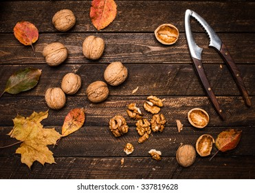 Walnut kernels whole walnuts and autumn leaves on dark rustic old wooden table. Walnuts and nutcracker on wooden background.