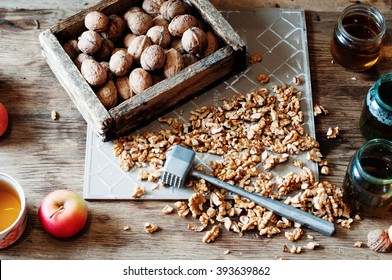 Walnut kernels and whole walnuts on rustic old wooden table. Whole and chopped walnuts on old wooden table. Walnuts.Whole walnuts,walnuts kernels and nutcracker.