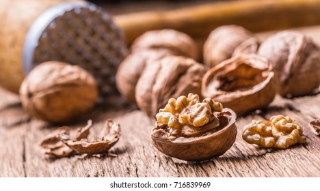 Walnut kernels and whole walnuts on rustic old oak table.