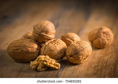 Walnut kernels and whole walnuts on rustic old oak table France