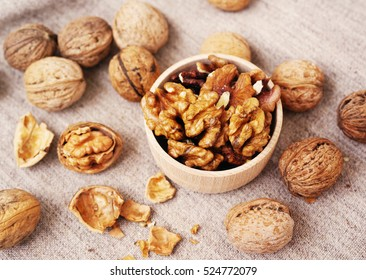 Walnut kernels in a wooden bowl and whole walnuts on table. Walnuts