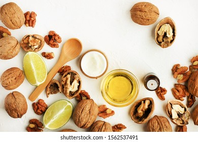 Walnut oil in jar, natural cosmetic product, lime slices and nuts on white table top view, holistic ingredients for homemade beauty treatment