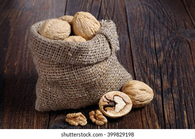 Walnut in sack and walnuts kernels on rustic old wooden table