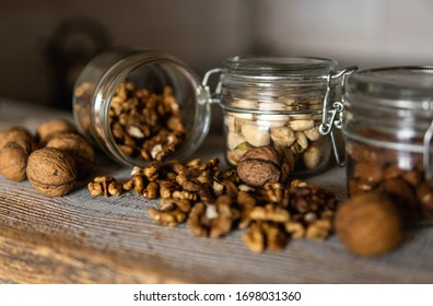 Walnut scattered on the white vintage table from a jar whith a whole walnuts. Walnut is a healthy vegetarian protein nutritious food. Walnut kernels and whole walnuts on rustic old wood.