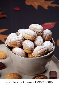Walnut shaped cookies on a plate, with bits of chocolate, heart shaped sugar cubes and walnuts. Russian oreshki.