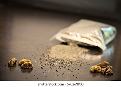 Walnut, spilled chia seed bag on kitchen table V1. Antioxidant foods for brain and heart health, high in omega 3 & 6. Vitamins and minerals, all essential amino acids. Combats cancer.
