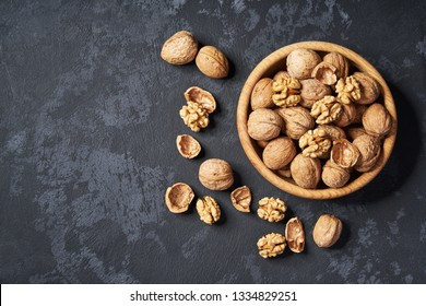 Walnut in wooden bowl on black background with copy space.Top view. Wooden plate with walnut on black background. Space for text