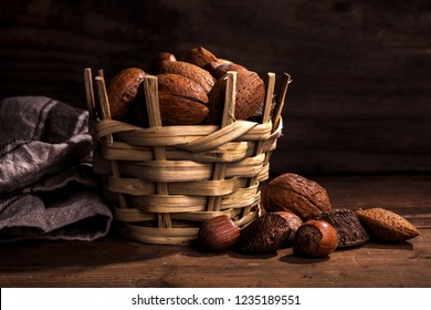 walnuts, almonds, brazil nuts  and hazelnuts in a basket on wooden background