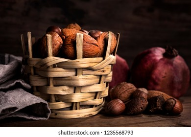 walnuts, almonds, brazil nuts, hazelnuts and pomegranates on wooden background