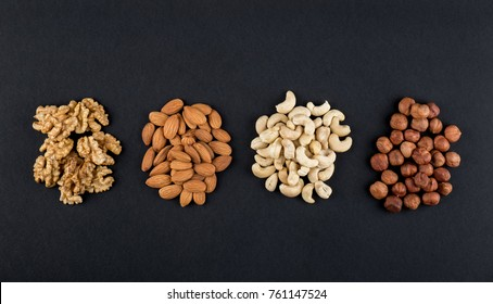 Walnuts, almonds, cashews and hazelnuts isolated on black with copy space. Raw food ingredients top view